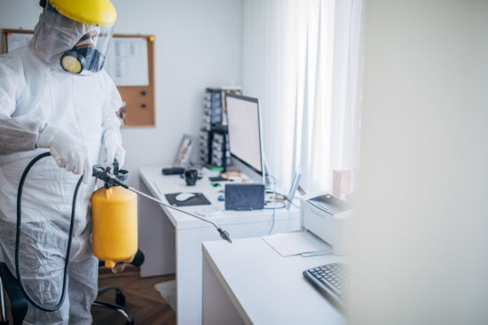 One man in protective suit disinfecting office work space