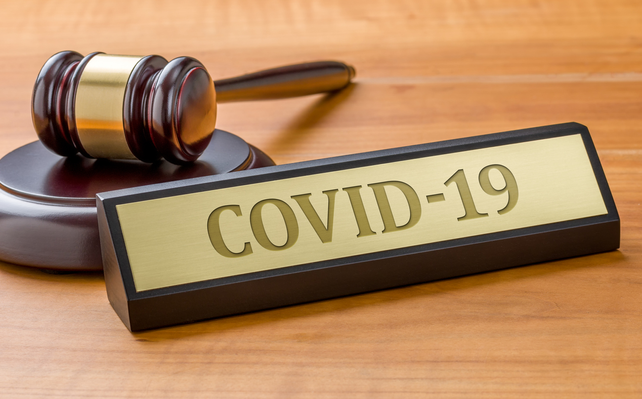 A gavel and a name plate with the engraving COVID-19